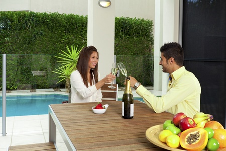 Young couple toasting with champagne in a modern backyard photo