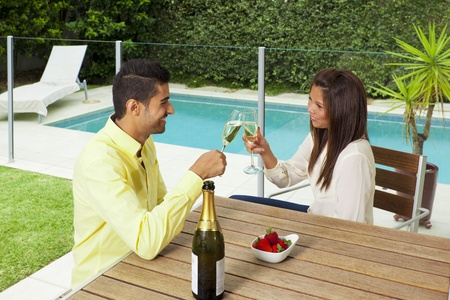 Young couple toasting with champagne in a modern backyard with swimming pool photo
