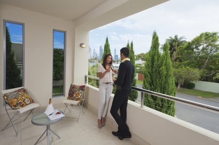Young couple toasting with champagne on a modern balcony overlooking the city photo