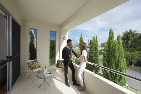 balcony view: Young couple toasting with champagne on a modern backyard overlooking the city
