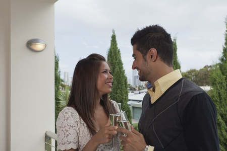 Young couple toasting with champagne on balcony overlooking the city photo