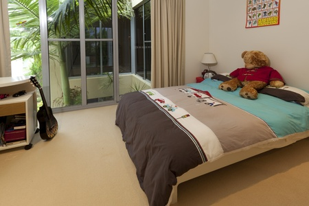 Young boys bedroom with bed, guitar and teddy bear photo