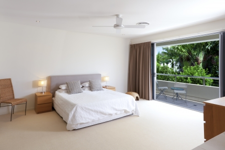 Large master bedroom with king size bed and balcony photo
