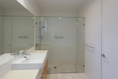 bad fliesen: Einfache Badezimmer mit Dusche, Waschbecken und Spiegel