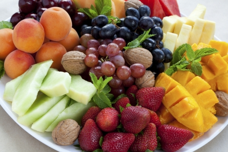 cherry varieties: Mixed fruit platter with strawberries, mango, cantaloupe, grapes, apricots, walnuts and mint Stock Photo