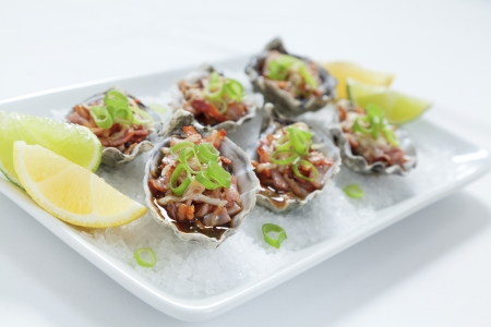 entree: Oven baked oysters kilpatrick on a bed of rocksalt with lemon and lime Stock Photo