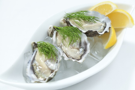 Fresh Hawkesbury river oysters on ice with lemon wedges Stock Photo