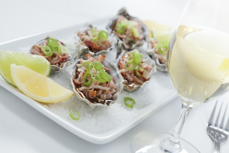 wine and food: Oven baked oysters kilpatrick on a bed of rocksalt with lemon and lime Stock Photo