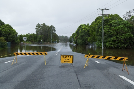 Flooded road with road block and flooded roas sign  photo