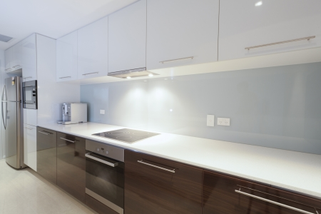 Stylish new kitchen with stainless steel oven, stove, coffee machine and fridge  photo