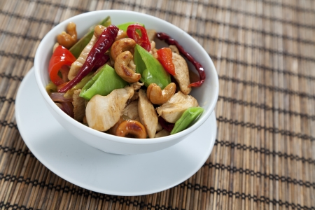 stir: Chicken with cashew nuts, chili, peas, capsicum on white background