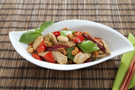 chicken chop: Chicken with cashew nuts, chili, capsicum and snow peas on a bamboo mat with chop sticks