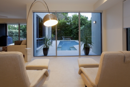 Two stylish recliners overlooking a swimming pool in luxurious house photo