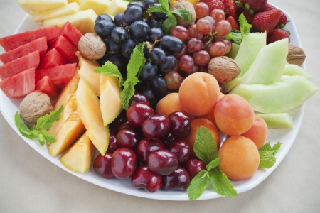 plato de comida: Verano colorido plato de frutas con piña, sandía, cerezas, albaricoques, fresas, melón, nueces y menta