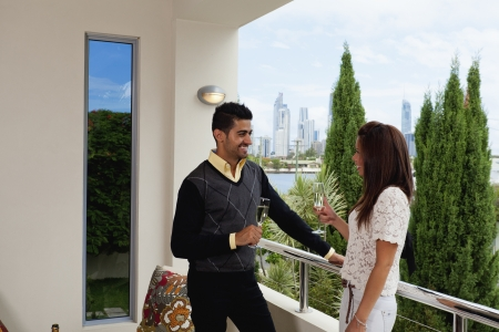 Young couple toasting on balcony overlooking the city photo