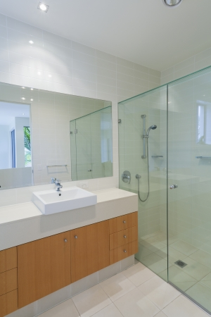 bathroom mirror: Clean, stylish bathroom with shower, sink and mirror