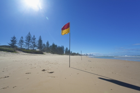 Lifeguard flag on sunny Gold Coast beach with Surfers Paradise in the background, Australia. Stock Photo - 13749975