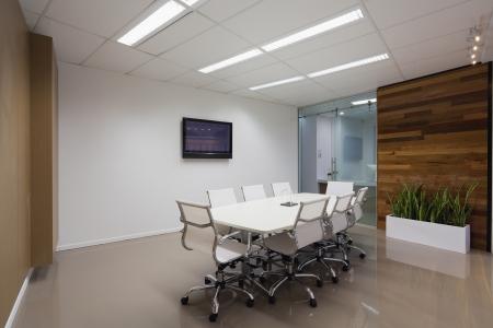 Nueva sala de juntas con mesa, sillas y una pantalla de plasma. Foto de archivo
