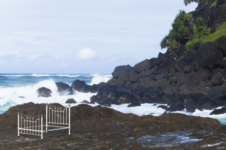 Iron bed frame on beach rocks Stock Photo - 13750008