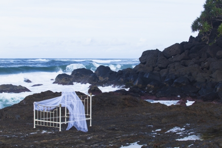 Iron bed frame and mosqito net on beach rocks Stock Photo - 13750006