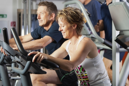 excercise: Mature couple working out at fitness centre on excercise bikes Stock Photo