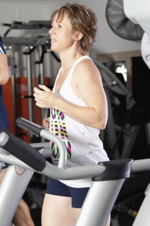 Mature woman running on tradmill at fitness centre Stock Photo - 13749980