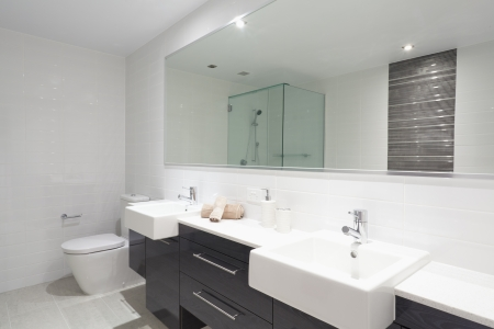 Modern twin bathroom with sinks, toilet and shower. photo