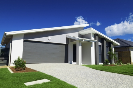 New suburban Australian house with small SOLD sign. Stock Photo