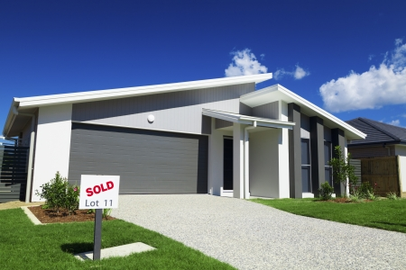 sold small: New suburban Australian house with small SOLD sign. Stock Photo
