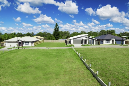 australian landscape: Sunny, green Australian housing development land with three newly built houses.