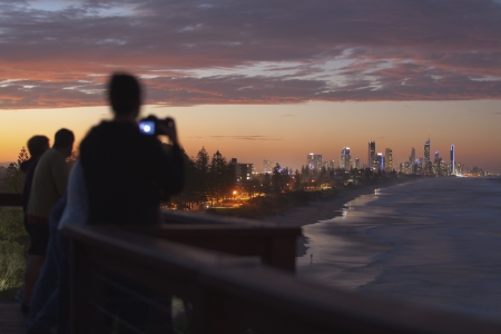 Tourists photographing the Gold Coast during a beautiful sunset. photo
