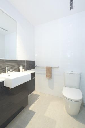 toilet sink: Peque�o cuarto de ba�o moderno con inodoro, lavabo y espejo Foto de archivo