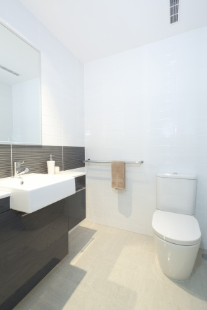 Small modern bathroom with toilet, sink and mirror