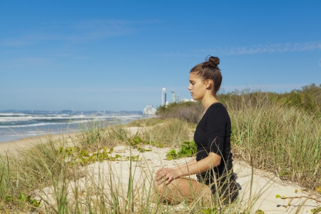 Young attractive woman doing Buddah yoga pose on pristine beach  photo