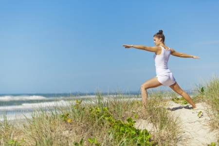 Young attractive woman doing warrior yoga pose on pristine beach  Stock Photo - 14179828