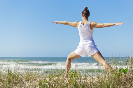 Young attractive woman doing warrior yoga pose on pristine beach  Stock Photo - 14179826