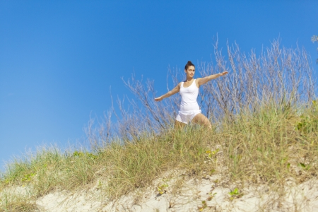 Young attractive woman doing warrior yoga pose on pristine beach  photo