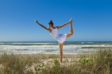 Young attractive woman doing dancers yoga pose on pristine beach  photo