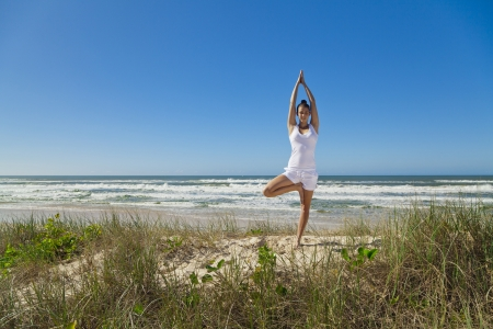 Young attractive woman doing tree yoga pose on pristine beach  photo