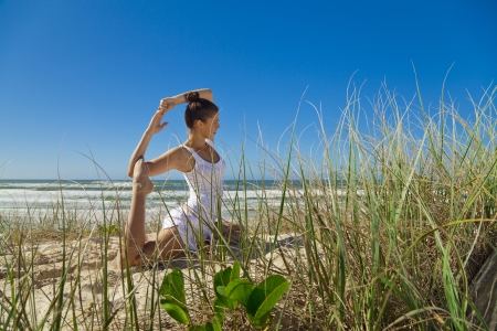 Young attractive woman doing pigeon yoga pose on pristine beach  photo