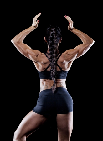 Female bodybuilder working out isolated on black