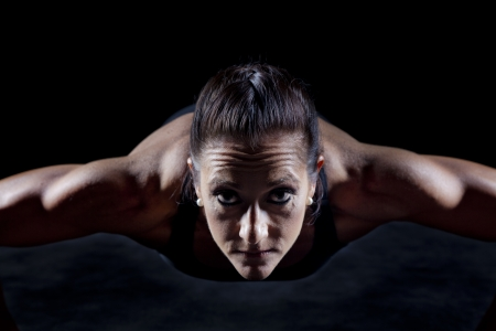 Female bodybuilder working out isolated on black photo