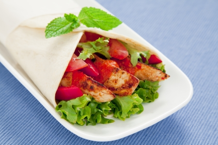capsicum: Healthy chicken tortilla wrap with lettuce, tomatoes, capsicum and  peri peri sauce Stock Photo