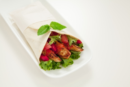 Healthy chicken tortilla wrap with lettuce, tomatoes, capsicum and  peri peri sauce photo