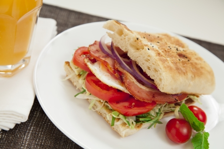 turkish bread: Healthy bacon and egg burger with onions, tomatoes and lettuce on turkish bread.