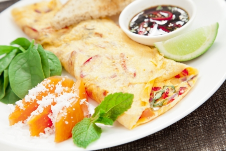 Healthy omelette with chillies, coriander, paw paw, spinach lime and spicy soy sauce photo