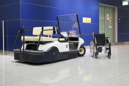 handicapped person: Wheelchair and buggy in airport terminal