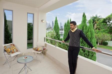 Junge männliche steht auf einem modernen Balkon mit Blick auf die Stadt Standard-Bild