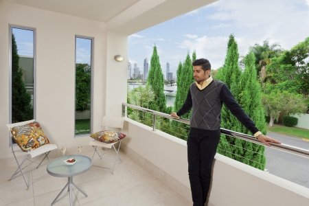 single family home: Young male standing on a modern balcony overlooking the city