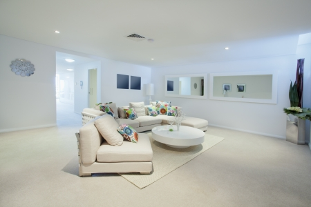 living space: Modern living room with couch and round table in new Australian apartment